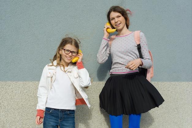 Mädchen, die an der abstrakten telefonbanane sprechen