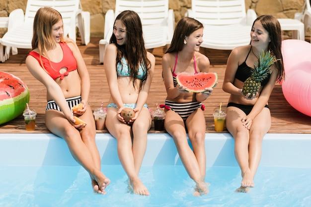 Mädchen, die an einander lächeln und früchte halten