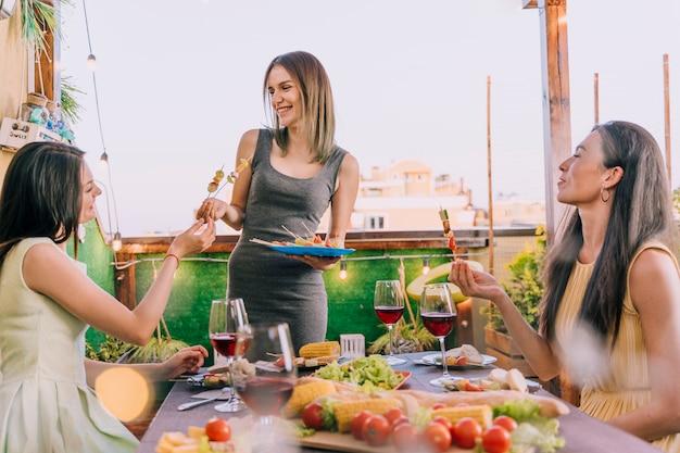 Mädchen, die aperitifs an der dachspitzenparty essen