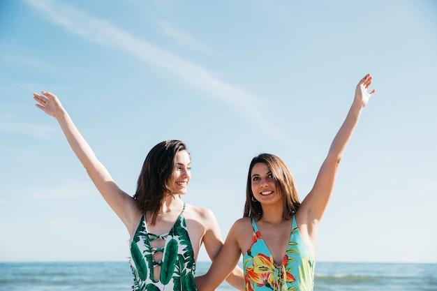 Mädchen, die arme am strand anheben