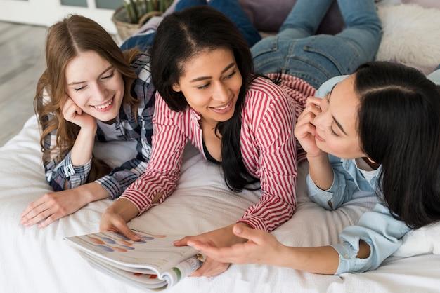 Mädchen, die auf bett liegen und zeitschrift lesen