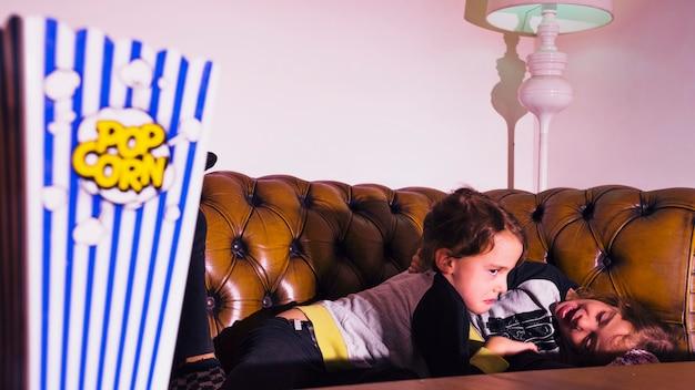 Mädchen, die auf couch mit fernsehen an spielen