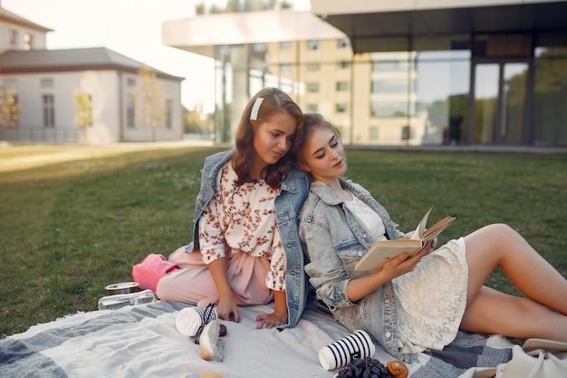 Mädchen, die auf einer decke in einem sommerpark sitzen