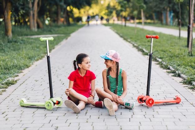 Mädchen, die auf gehweg mit ihren stoßrollern auf gehweg im park sitzen