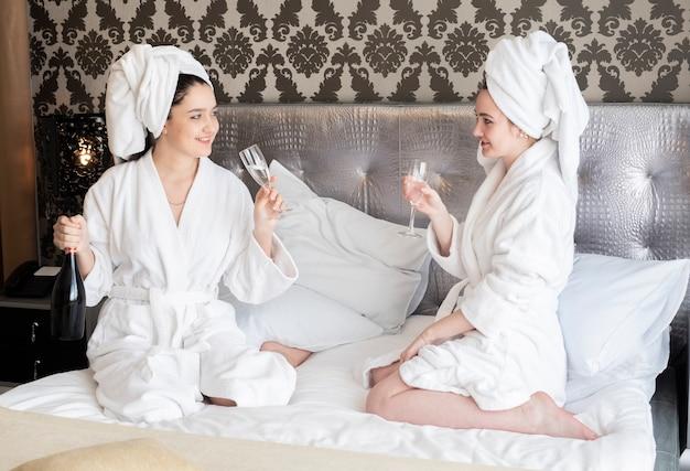 Mädchen, die badekurorttag mit einem glas champagner genießen