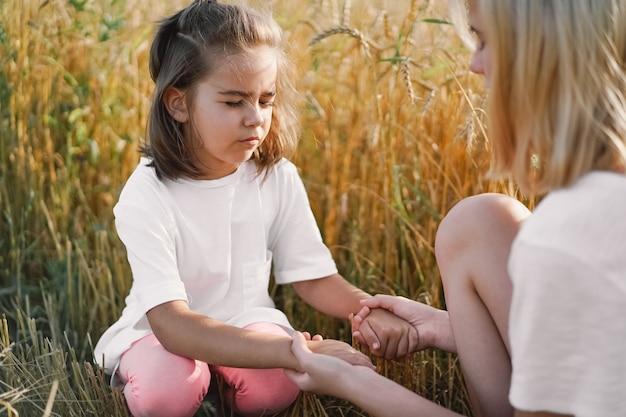 Mädchen, die beten und hände in einem weizenfeld halten. beten sie, dass gott sich gegenseitig unterstützt.