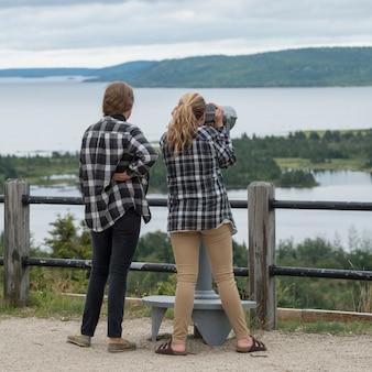 Mädchen, die buchtblick durch ein münzfernglas, joey lookout, gambo, neufundland betrachten an