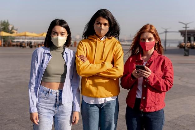 Mädchen, die draußen medizinische masken tragen