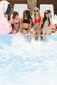 Mädchen, die einander swimmingpool betrachten