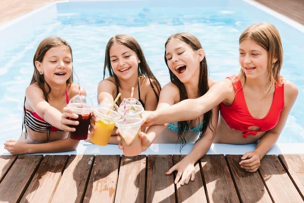Mädchen, die einen toast im swimmingpool geben