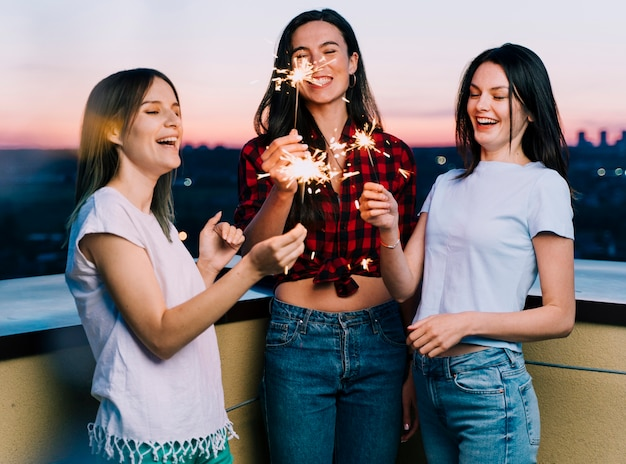 Mädchen, die feuerwerke auf dachspitze an der dämmerung halten