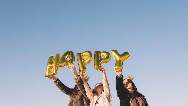 Mädchen, die glückliches schreiben von den ballonen halten