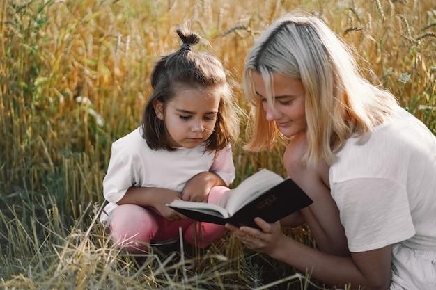Mädchen, die heilige bibel in einem weizenfeld lesen. studiere gemeinsam die heilige bibel.