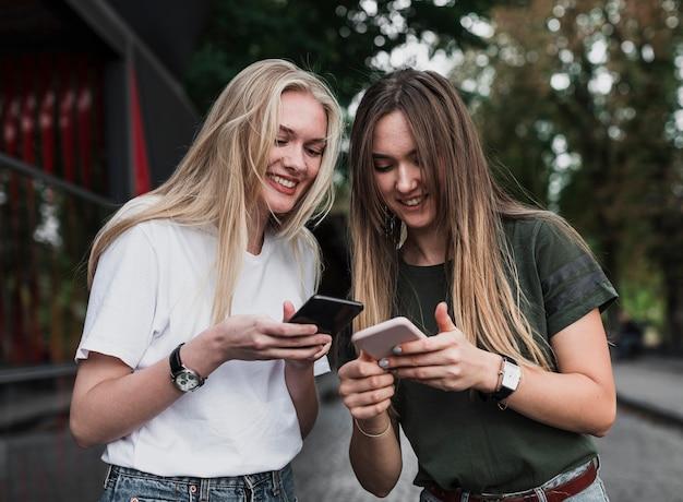 Mädchen, die ihre mitteilungen auf telefonen überprüfen