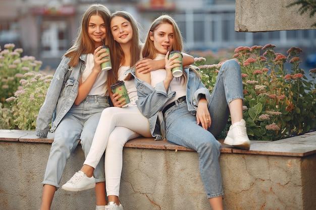 Mädchen, die in einer frühlingsstadt gehen und kaffee in ihrer hand halten