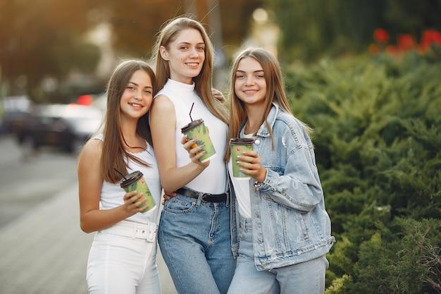 Mädchen, die in einer frühlingsstadt gehen und kaffee nehmen