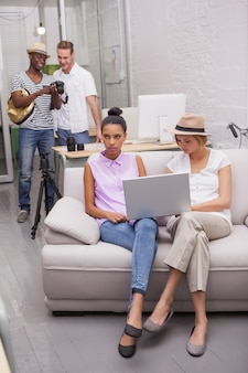 Mädchen, die laptop mit jungen im hintergrund verwenden