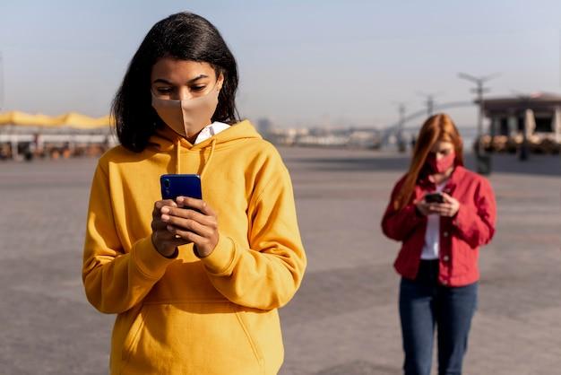 Mädchen, die medizinische masken tragen, während soziale distanz