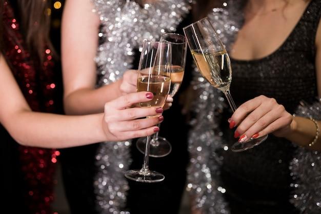 Mädchen, die mit champagner an der party des neuen jahres rösten