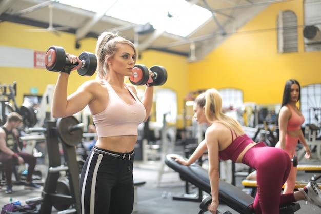 Mädchen, die mit gewichten an der turnhalle ausbilden