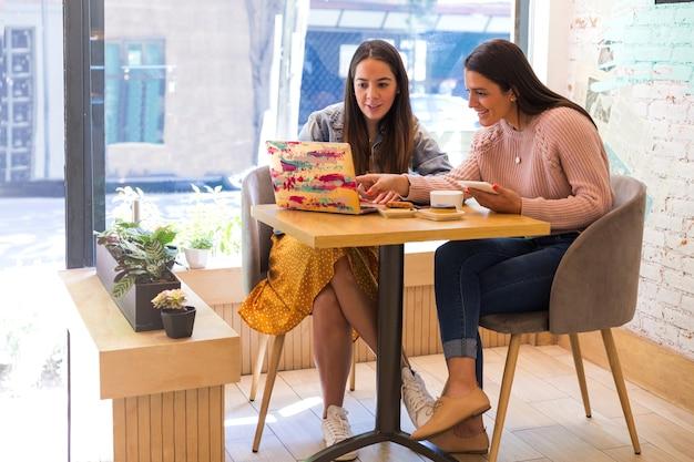 Mädchen, die mit ihrem computer in einem café arbeiten