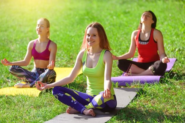 Mädchen, die morgens yoga draußen im wald aufwerfen