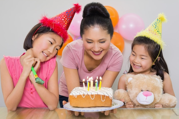 Mädchen, die mutter mit kuchen an einer geburtstagsfeier betrachten