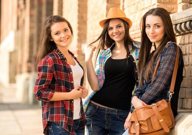 Mädchen, die nahe der universität lächeln und zusammen stehen.