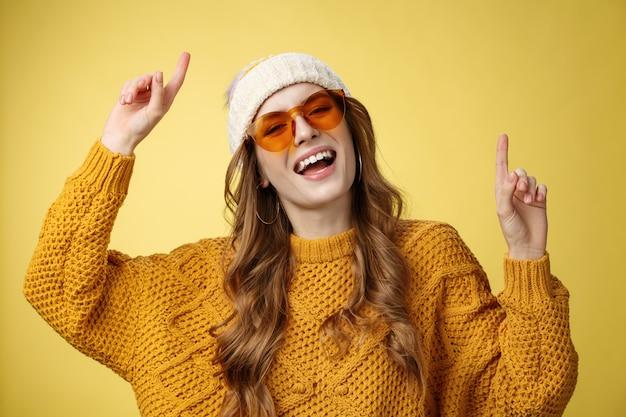 Mädchen, die party genießen, haben spaß, lächeln im allgemeinen glücklich und starren die kamera an, die zeigefinger anhebt, tanzen ...