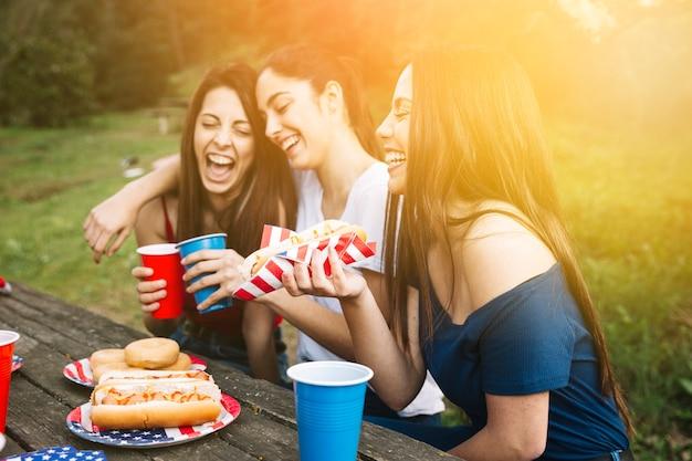 Mädchen, die picknick auf sonnenuntergang haben