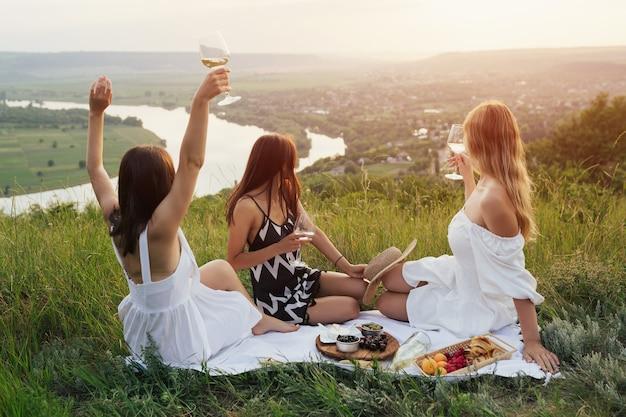Mädchen, die picknickzeit und schöne landschaft vom hügel im sonnigen sommertag genießen
