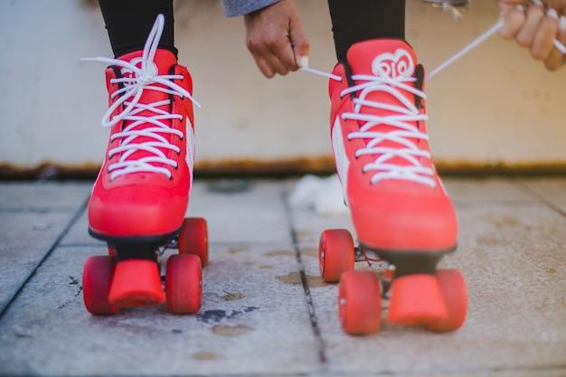 Mädchen, die rote rollen mit weißen schnürsenkeln bindet