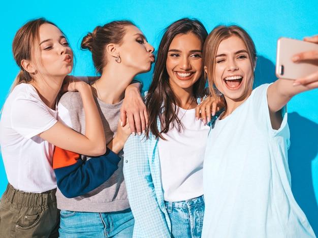 Mädchen, die selfie selbstporträtfotos auf smartphone machen modelle, die nahe blauer wand im studio, frau zeigt positive gesichtsgefühle aufwerfen