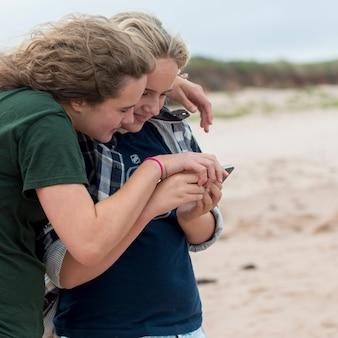 Mädchen, die smartphone auf dem strand, york point, prinz edward island, kanada aufpassen