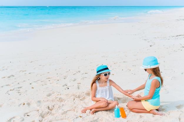 Mädchen, die sonnenschutzmittel auf einander am strand auftragen. das konzept des schutzes vor ultravioletter strahlung