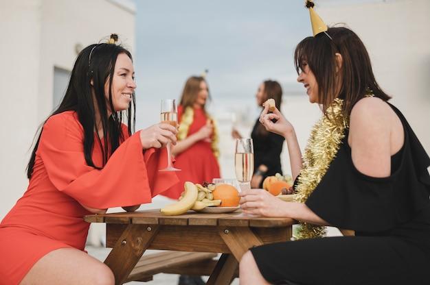 Mädchen, die spaß auf einer party auf der dachspitze haben