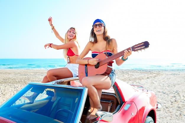Mädchen, die spaß haben, gitarre am th strand in einem auto zu spielen