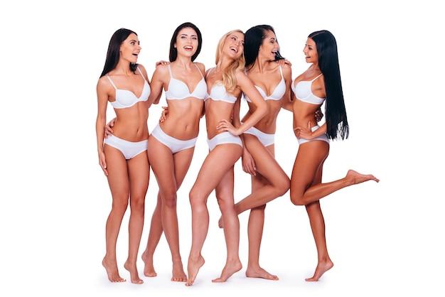 Mädchen, die spaß haben. in voller länge von fünf schönen frauen in dessous, die natürlich posieren und aussehen, während sie zusammen vor weißem hintergrund stehen