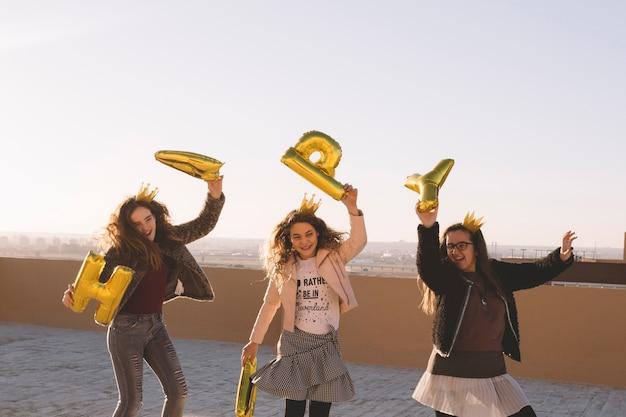 Mädchen, die spaß mit buchstabenballonen haben