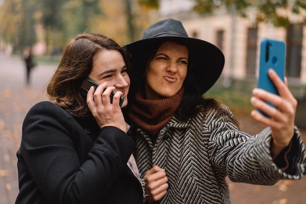 Mädchen, die telefon für videoanruf an freunde im park verwenden