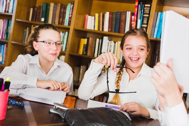 Mädchen, die über bild im schulkopiebuch lachen