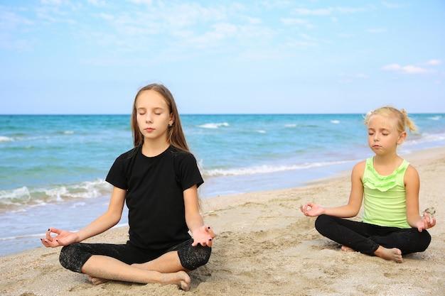 Mädchen, die yoga am strand praktizieren