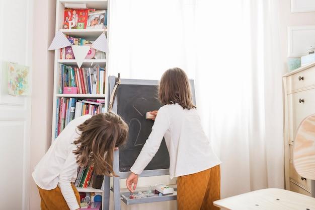 Mädchen, die zeichnungen von der tafel abwischen