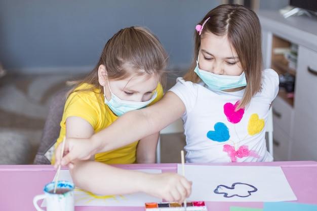 Mädchen, die zu hause während der quarantäne in sterilen masken zusammen zeichnen. kinderspiele, zeichenkunst, zu hause bleiben konzept