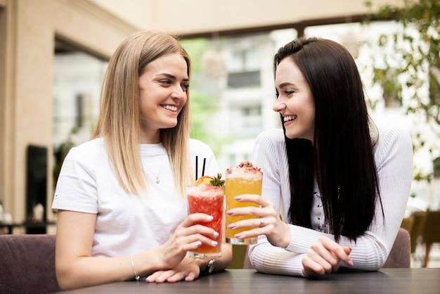 Mädchen, die zuhause mit ihren cocktails rösten