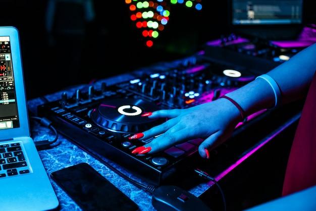 Mädchen dj mischt musik mit ihren händen auf einem musikmischer in einem nachtclub auf einer party