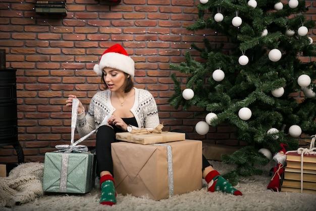 Mädchen durch den weihnachtsbaum, der geschenke auspackt