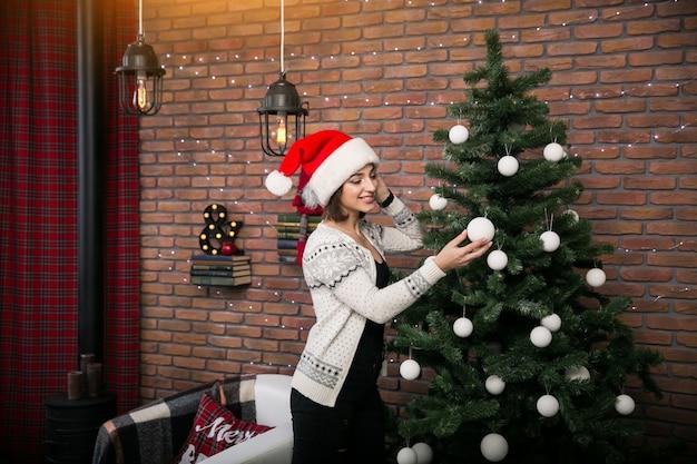 Mädchen durch den weihnachtsbaum in einem roten hut