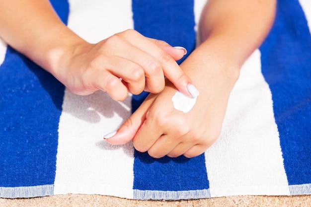 Mädchen entspannt sich auf dem handtuch auf dem sand am strand und trägt sonnencreme auf ihre hand auf