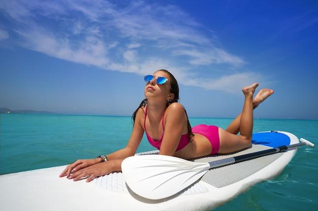 Mädchen entspannte sich auf paddel surf board sup liegen